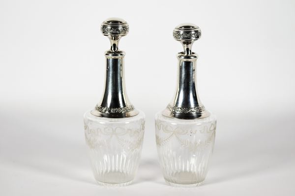 Pair of antique engraved crystal bottles with silver-coated neck and cap