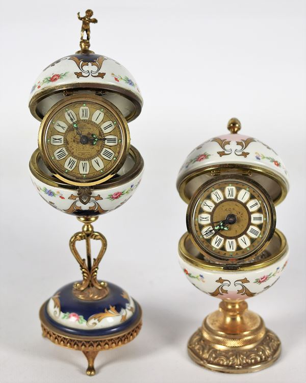 Lot of two alarm clocks enclosed in porcelain spheres with gilded metal bases
